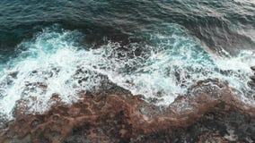 Cierre aéreo encima del abejón tirado de la costa rocosa de la isla de Chipre lavada por las ondas grandes del mar en la tormenta almacen de metraje de vídeo