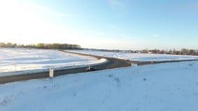 CIERRE AÉREO ENCIMA del vuelo sobre la conducción de automóviles a lo largo de un camino nevoso en la salida del sol de oro Autom almacen de metraje de vídeo