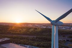 Cierre aéreo para arriba tirado de una turbina de viento delante de una puesta del sol perfecta imágenes de archivo libres de regalías