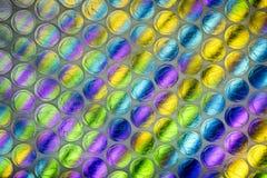 Cierre abstracto encima de la hoja del plástico de burbujas con el fondo colorido imagenes de archivo