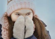 Cierre adolescente de la muchacha encima del retrato en sombrero y manoplas hechos punto Imagen de archivo libre de regalías