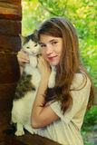 Cierre adolescente del gato del abrazo del gril encima de la foto Fotografía de archivo libre de regalías