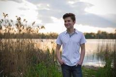 Cierre adolescente del muchacho encima del retrato en el fondo de la naturaleza del lago del verano Fotografía de archivo libre de regalías