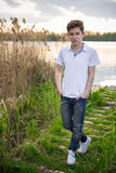 Cierre adolescente del muchacho encima del retrato en el fondo de la naturaleza del lago del verano Imagen de archivo libre de regalías