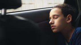 cierre Adolescente que duerme en el asiento trasero del coche almacen de video