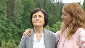 Cierre al aire libre encima del retrato de la madre mayor caucásica feliz sonriente con su hija adulta que abraza y que mira metrajes