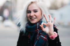 Cierre al aire libre encima del retrato de la muchacha sonriente feliz hermosa joven que muestra gesto aceptable Looking modelo e Foto de archivo libre de regalías