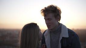 Cierre al aire libre encima del retrato de los pares elegantes felices jovenes que abrazan en el tejado en la puesta del sol o la almacen de video