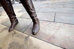 Cierre anguloso para arriba de las piernas del ` s de la mujer y de las botas sucias imagenes de archivo