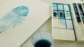 Cierre azul de la macro del pintor de la acuarela para arriba en el fondo blanco almacen de video