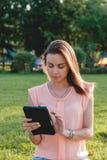 Cierre colorido para arriba de la muchacha que usa la tableta en el parque Fotografía de archivo