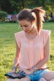 Cierre colorido para arriba de la muchacha que usa la tableta en el parque Imagen de archivo