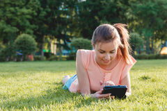 Cierre colorido para arriba de la muchacha que usa la tableta en el parque Fotos de archivo