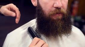Cierre cosechado encima del propósito de peinar la barba rizada marrón con el cepillo en manos cosechadas del peluquero antes de  metrajes