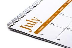 Cierre de escritorio de julio del calendario para arriba en el fondo blanco Foto de archivo