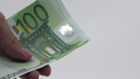 Cierre de la cámara lenta encima de las manos que cuentan cuentas de los euros de ciento Dinero de la cuenta metrajes