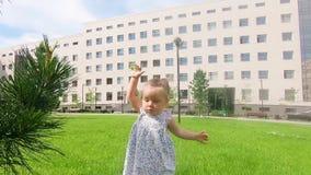 Cierre de la cámara lenta para arriba: bebé lindo que camina en el parque de la ciudad y el aroun de exploración del mundo ella,  metrajes