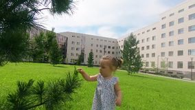 Cierre de la cámara lenta para arriba: bebé lindo que camina en el parque de la ciudad y el aroun de exploración del mundo ella,  almacen de metraje de vídeo