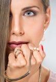 Cierre de la cabeza de la cara de la mujer joven de la belleza encima de la mano del oro del collar de la joyería Imagenes de archivo