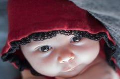 Cierre de la cara del bebé para arriba, con los ojos hermosos grandes Recién nacido en una c roja foto de archivo libre de regalías
