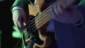 Cierre de la guitarra baja para arriba Hombre que toca la guitarra en el concierto de rock vídeo de 4K UHD almacen de metraje de vídeo