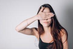 Cierre de la mujer joven ella ojos con la mano foto de archivo