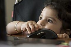 Cierre de la niña encima del retrato que juega con el ordenador portátil imagenes de archivo