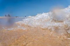 Cierre de la onda del mar encima de la playa cercana en la arena fotografía de archivo libre de regalías