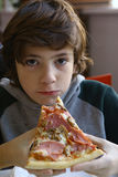 Cierre de la pizza de los alimentos de preparación rápida de la consumición del muchacho del adolescente encima de la foto Fotografía de archivo