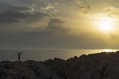 Cierre de la situación del hombre el mar adriático en Croacia en la puesta del sol que sostiene los brazos hacia fuera Fotografía de archivo libre de regalías