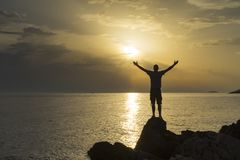 Cierre de la situación del hombre el mar adriático en Croacia en la puesta del sol que sostiene los brazos hacia fuera Imagen de archivo