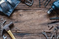 Cierre de la visión superior para arriba de las herramientas prácticas y de los vaqueros de la variedad en el backg de madera Imagenes de archivo