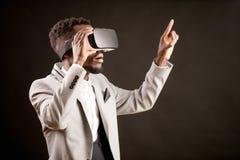 Cierre de la vista lateral encima de la imagen del varón del Afro con los vidrios de la realidad virtual Imagenes de archivo