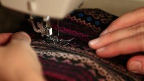 Cierre de mano encima del tiro del material de costura de la mujer con la máquina de coser eléctrica almacen de video