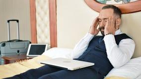 Cierre de trabajo del acabamiento masculino del hombre de negocios usando el ordenador portátil que tiene dolor de cabeza en el v almacen de video