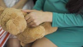 Cierre de un oso de peluche amarillo suave. Manos femeninas sosteniendo el regalo. Mujer embarazada con vestido verde-azul seda co almacen de video