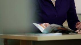 Cierre del ángulo bajo para arriba del empleado que muestra el folleto al cliente almacen de metraje de vídeo