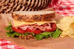 Cierre del bocadillo del jamón y del queso de la cesta de la comida campestre para arriba foto de archivo libre de regalías