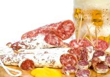 Cierre del bocado de la cerveza y de la carne para arriba Fotografía de archivo