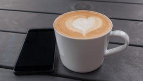 Cierre del concepto de la tecnología, del negocio y de la vida moderna para arriba de la taza del smartphone y de café en la tabl Imagen de archivo libre de regalías