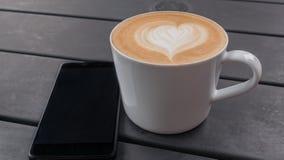 Cierre del concepto de la tecnología, del negocio y de la vida moderna para arriba de la taza del smartphone y de café en la tabl Imagenes de archivo