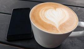 Cierre del concepto de la tecnología, del negocio y de la vida moderna para arriba de la taza del smartphone y de café en la tabl Foto de archivo libre de regalías
