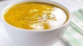 Cierre del cuenco blanco con la sopa de la calabaza del cabotia foto de archivo