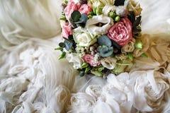 Cierre del detalle del vestido de boda para arriba y flores Imágenes de archivo libres de regalías