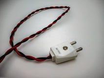 cierre del enchufe eléctrico encima del tiro con el alambre rojo en un fondo blanco fotografía de archivo