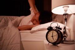 Cierre del hombre sus oídos a mano del ruido del despertador en cama imágenes de archivo libres de regalías