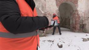 Cierre del ingeniero de construcción para arriba usando la tableta con el trabajador en fondo almacen de metraje de vídeo