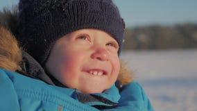 Cierre del invierno encima del retrato al aire libre del bebé soñador adorable, bebé feliz que juega en la nieve, al aire libre metrajes