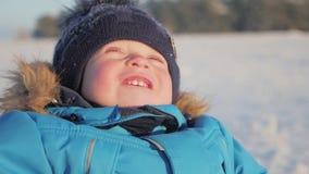 Cierre del invierno encima del retrato al aire libre del bebé soñador adorable, bebé feliz que juega en la nieve, al aire libre almacen de video