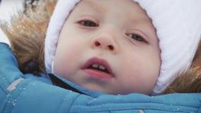 Cierre del invierno encima del retrato al aire libre del bebé soñador adorable, bebé feliz que juega en la nieve, al aire libre almacen de metraje de vídeo